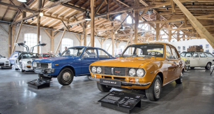 Mazda R100 (modrá) z roku 1971 s dvourotorovým  motorem Wankel. Vedle typ RX-2 ze stejného roku s větším motorem, řadící se o segment výše do střední třídy