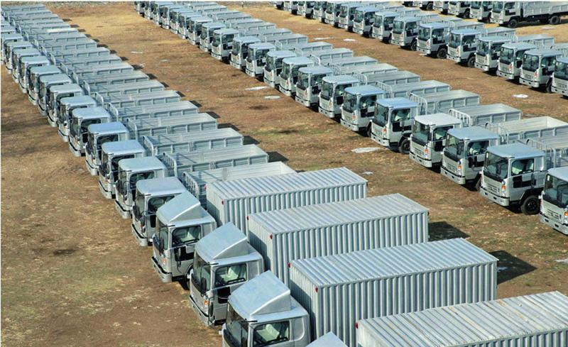 Nové pětitunové rozvážkové (valníky askříně) automobily Sungri naparkovišti utovárny.