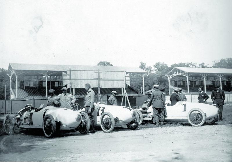 Tým Benz svozy Benz Tropfenwagen vboxech Velké ceny Itálie 1923. Zleva: st. č. 7 Franz Horner, st. č. 13 Willy Walb ast. č. 1 Ferdinando Minoia.