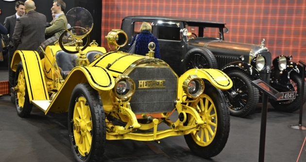 Ve své době slavný Mercer Racebout (1912), šasi 35-D- -378. Vynikal rychlostí a přitom spolehlivostí. Značku založila roku 1909 rodina Roeblingových. Tito američtí inženýři vydělali peníze stavbami vyplétaných lávek zocelových lan. Vzadu Bentley 4,5 l Weyman Saloon (1929)
