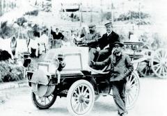 Týden vNice 26. a27. března 1900, Závod cestovních vozidel Nice-Draguignan-Nice (296 km). Vítěz třídy E. T. Stead aWilhelm Bauer zařidítky závodního vozu Daimler Phoenix smotorem omaximálním výkonu 28 k(startovní číslo 106). Vedle vozu stojí Herman Braun – on nakonec fatální nehodu, která se uděje vzápetí postartu dozávodu dovrchu, přežije, Bauer nikoliv.