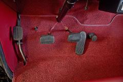 Pět pedálů. Zleva zajišťovací brzda, spojka, brzda, plyn a startér