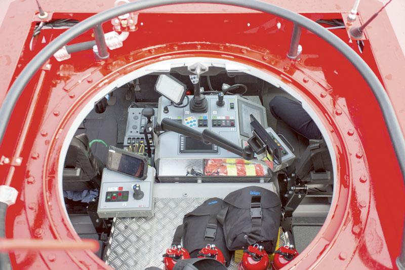 Kabina má ve střeše zabudovaný kruhový průlez.