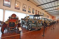Defilé nejstarších automobilů. Na stěnách jsou plakáty příležitostných automobilových výstav muzea. Za požárními automobily se tyčí mohutný DeDion-Bouton 24CV