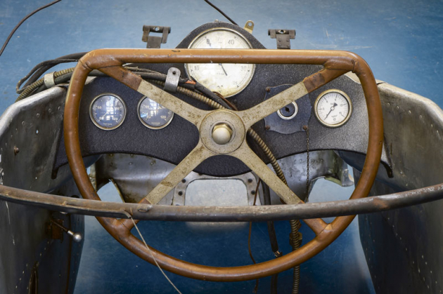 Otáčkoměr uprostřed, po levé straně dva teploměry (motorový olej, chladící médium), po pravé straně spínač elektromagneta a zcela vpravo tlakoměr motorového oleje. Volant je v opačné, nepřirozené pozici.