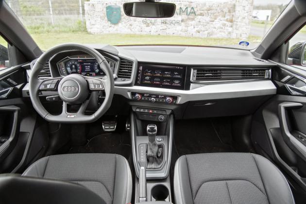 Palubní deska je technicistní a drží se typického stylu Audi. Výrazným prvkem interiéru je volant se zploštělou spodní částí věnce