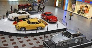 Trojlístek Porsche 356, v pozadí traktor  Porsche Diesel Standard P128 a nejblíže  Porsche 911 S (1972) se vzduchem chlazeným šestiválcem 2341 cm3 (190 k) v centrální dvoraně. Vypreparovaný motor 911 S byl kprohlédnutí vhlavním vstupu