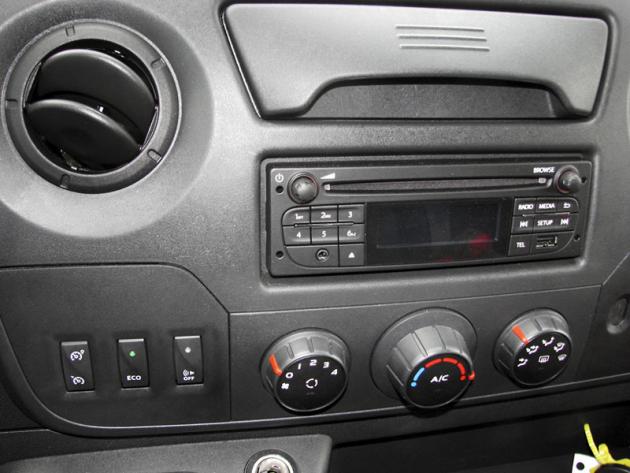 Na středovém panelu jsou rozhlasový přijímač a další ovladače. Krátkou pákou vlevo pod volantem se volí režim jízdy