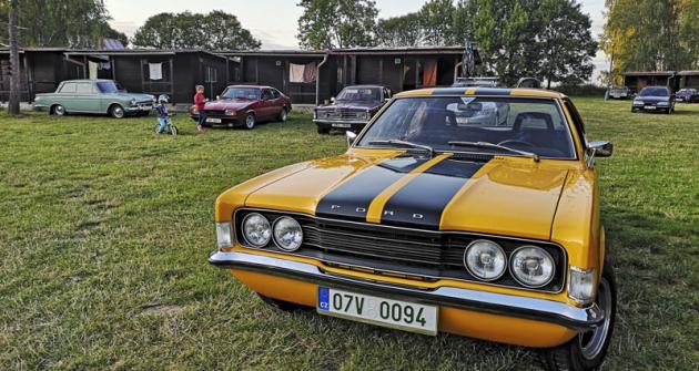 Typické páteční zátiší. V popředí Cortina Mk. III Marcela Truhláře, vpozadí další klasické Fordy apobíhající děti