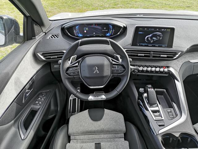 Originálně řešená palubní deska s odděleným prostorem pro řidiče a nad malým volantem umístěnými hlavními přístroji samozřejmě zůstává přítomná také u hybridního provedení