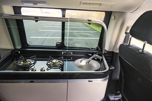 Kuchyňka s dvojicí hořáků a dřezem disponuje krycím sklem sloužícím v zavřené poloze jako polička nebo pracovní kuchyňská deska