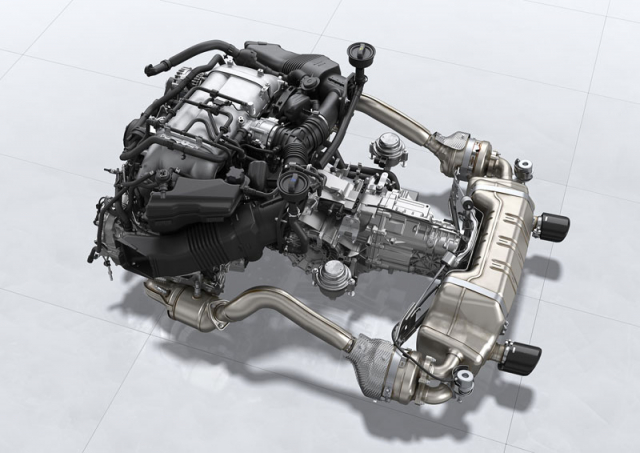 Uspořádání hnací soustavy s motorem před zadní nápravou a převodovkou za ní. Výfuková soustava má společný tlumič pro obě větve. Vidět jsou také dva aktivní silentbloky uložení motoru PADM (Porsche Active Drivetrain Mounts) po stranách převodovky