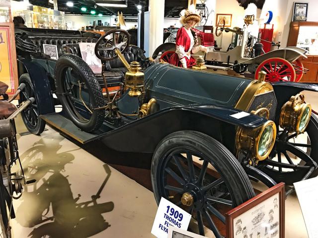 Pětimístný Thomas Flyer 6-40 Flyabout (1909) se šestiválcem 4,38litru (40 k) a třístupňovou převodovkou. Podobný Thomas Flyer zvítězil v ročníku 1908 v nikdy nepřekonaném závodě New York toParis (1908) dlouhém 35 000 km. Ze šesti týmů dojely do cíle tři vozy. Firma Thomas Flyer existovala v letech 1900 – 1919