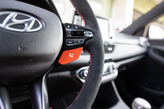 Volant čalouněný Alcantarou má oranžová tlačítka pro volbu jízdního režimu. Praktická je možnost aktivovat/deaktivovat automatické meziplyny tlačítkem REV přímo na volantu (mají ji i standardní i30 N)
