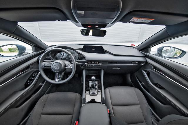 Palubní deska Mazdy 3 se snaží minimalizovat vše kromě volantu, přístrojů a řadicí páky. Displej navigace je umístěný příjemně daleko od posádky
