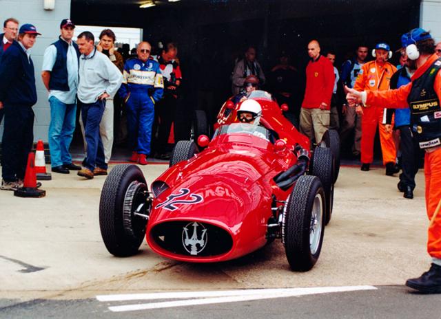 Stirling Moss (Maserati 250F) vyjíždí před někdejším soupeřem Tonym Brooksem (Ferrari 500) na trať při závodech veteránů vSilverstone (2000)