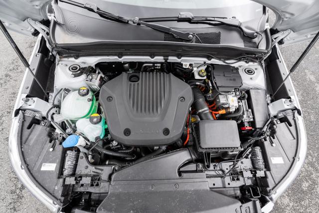 Pod velkým krytem je umístěný přeplňovaný zážehový tříválec 1,5litru, elektromotor je uložen nad převodovkou a pod vzduchovým filtrem