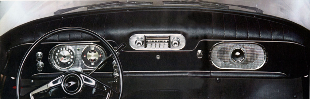 Symetricky střižená palubní deska spřístrojovým štítem vlevo areproduktorem rádia vpravo