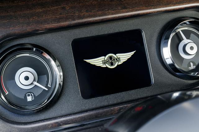 Před volantem je miniaturní displej palubního počítače, hlavní přístroje jsou uprostřed palubní desky
