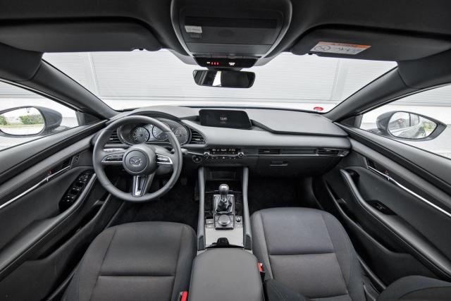 Palubní deska sází na vizuální čistotu a minimalismus. Tříramenný volant výborně padne do ruky, páčky pod ním jsou poměrně blízko věnci – to je dobré pro řidiče s menšíma rukama. Možnost nastavení v podélném i svislém směru je