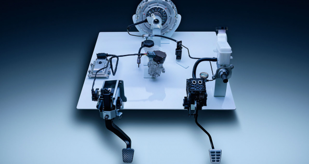 """V levé části snímku jsou komponenty spojky """"clutch-by-wire"""". Základními prvky jsou řídicí jednotka (TCU), nádobka spojkové kapaliny v jednom tělese s čerpadlem a centrální vypínací ložisko (CSC)"""