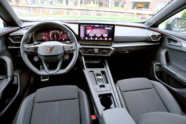 Palubní deska řidiče doslova obklopuje. Znamenitý volant dobře padne do rukou, ovladače jsou rozvrženy do přehledných celků. Řadu funkcí lze ovládat z volantu nebo hlasem. Dekorační detaily mají povrch v měděném odstínu