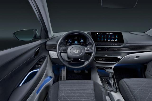 Specifický volant, širokoúhlý dotykový monitor multimediálního systému uprostřed izdánlivě průběžné linky výdechů ventilace připomínají dražší vozy Hyundai, zejména nový Tucson