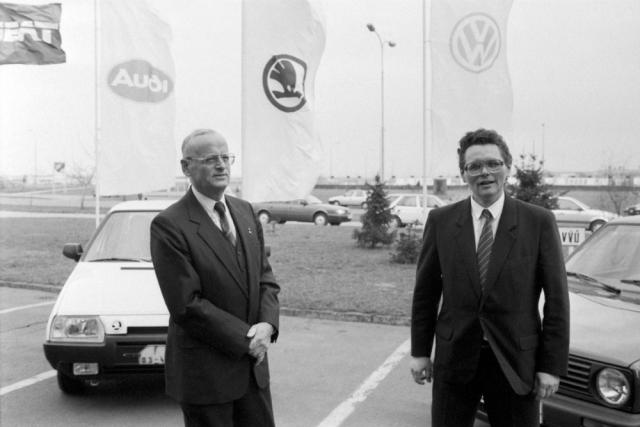 28. března 1991. Carl Hahn, předseda představenstva Volkswagen AG, a Petr Dědek, od roku 1987 podnikový ředitel AZNP, následně ředitel státního automobilového koncernu Škoda, po 16. 4. 1991 ředitel zbytkového státního podniku, který byl pak přejmenován na STASKO (Státní, případně Stará Škoda). Prof. Hahn symbolicky stojí před vozem Škoda Favorit a Petr Dědek před Volkswagenem Golf
