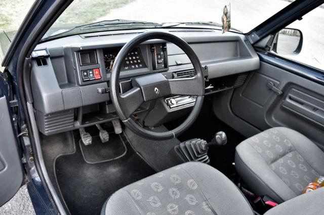 Přehledné pracoviště řidiče s několika zásadními ovládacími prvky. Zmoderního rádia znějí klasické tóny 80. let