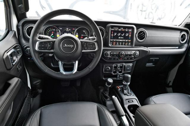 Pracoviště řidiče zůstává věrné ortodoxnímu charakteru Wrangleru. Tvary jsou tedy přísně účelové a poháněcí ústrojí se ovládá dvojicí velkých pák na středové konzole. V provedení 4xe došlo k úpravě částečně digitálního přístrojového štítu s ohledem na potřebu informovat řidiče o funkci hybridního ústrojí